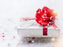 Witte giftdoos met rode boog op sneeuw met bokeh en sneeuwval exemplaarruimte voor uw ontwerp stock afbeeldingen
