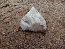 Witte glanzende steen met textuur op het zand geweven behang als achtergrond, strand Oceaan stock afbeeldingen