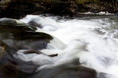 Witte glasheldere rivierstroom die over rotsen meeslepen stock fotografie