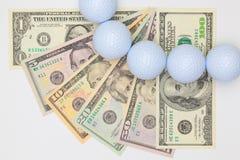 Witte golfballen en verschillend ons dollarbankbiljetten Royalty-vrije Stock Afbeelding