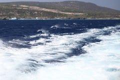 Witte golven van een jacht op een donkerblauwe overzees Stock Foto's