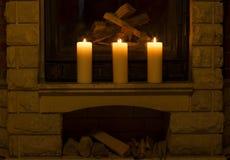 Witte grote kaarsen die zich op de open haard bevinden Stock Foto's