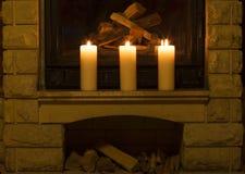 Witte grote kaarsen die zich op de open haard bevinden Stock Foto