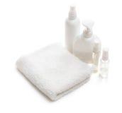 Witte handdoek en flessen met schoonheidsmiddelen royalty-vrije stock afbeelding