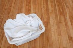 Witte handdoeken in een wasmand op houten vloer stock foto's