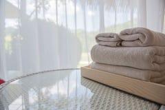 Witte handdoeken op de lijst op de ruimte en de witte gordijnenachtergrond stock afbeelding