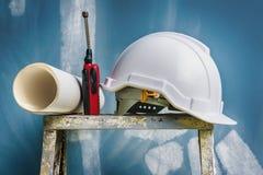 Witte helm met blauwdruk en radio die op de vouwende ladder worden geplaatst stock fotografie