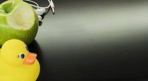 Witte hoofdtelefoons, een gele eend en een groene appel stock foto