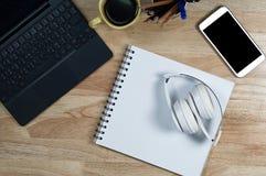Witte hoofdtelefoonsstapel op wit boekdocument op de houten lijst stock fotografie