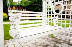 Witte houten bank zoals een schommeling In het park op een de zomermiddag stock foto's