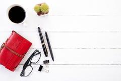Witte houten bureaulijst met rood notitieboekje stock foto's