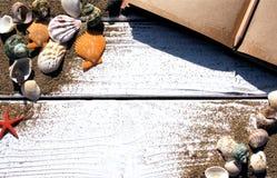 Witte houten raad met zand en shells, antiek notitieboekje Royalty-vrije Stock Afbeeldingen