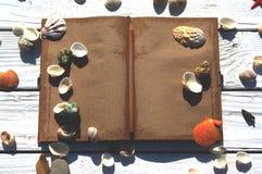 Witte houten raad met zand en shells, antiek notitieboekje Stock Fotografie