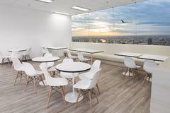 Witte houten stoelen in eetkamer van modern bureau met vensters stock foto