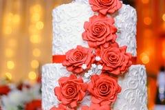 Witte huwelijkscake met rode suikergoedbloemen, close-up Stock Afbeelding