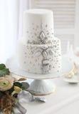 Witte huwelijkscake met zilveren decoratie Stock Afbeelding