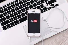 Witte iPhone 5s met plaats YouTube op het scherm en de hoofdtelefoons l Stock Foto's