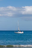Witte jachtzeilen in het overzees, kustlijn stock afbeelding