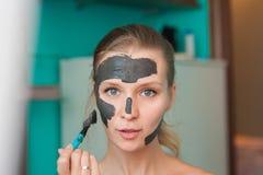 Witte jonge vrouw die een gezichtsmasker thuis op een turkooise achtergrond dragen Europese vrouw in zwart masker voor gezichts d stock afbeelding