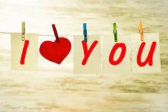 Witte kaarten en een rood hart die die op een koord hangen, met rode gespen met een teken van bekentenis van liefde wordt vastgem stock afbeeldingen