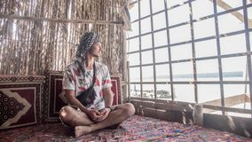 Witte Kaukasische mens in de Arabische sjaal die zitting in het traditionele Islamitische restaurant kijken royalty-vrije stock afbeelding