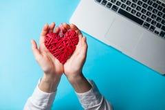Witte Kaukasische vrouwelijke handen die hart gevormd stuk speelgoed houden dichtbij lapto stock foto