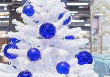 Witte Kerstboom die met blauwe ballen wordt verfraaid stock afbeeldingen