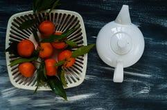 Witte ketel en mandarins met groene bladeren in een witte authentieke vaas voor fruit op een blauwe achtergrond Stock Fotografie