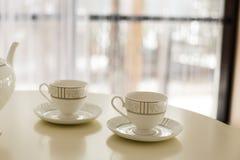 Witte ketel en twee koppen voor thee op de lijst royalty-vrije stock foto's