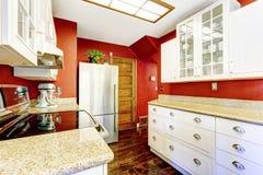 Witte keukenruimte met contrast heldere rode muren Royalty-vrije Stock Foto's