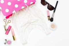 Witte kleding in een het winkelen zak en schoonheidsmiddelen op een witte backgroun stock afbeeldingen