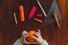Witte kleine handen van een Kaukasische tekening van het peuterkind met een oranje potlood op een oranje fruit stock afbeeldingen