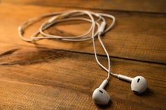 Witte kleine hoofdtelefoons op een houten geïsoleerde achtergrond Horizontaal kader Stock Fotografie