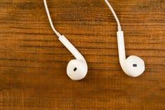 Witte kleine hoofdtelefoons op een houten geïsoleerde achtergrond Horizontaal kader Royalty-vrije Stock Afbeeldingen