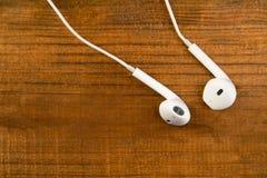 Witte kleine hoofdtelefoons op een houten geïsoleerde achtergrond Horizontaal kader Royalty-vrije Stock Fotografie