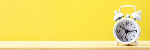 Witte kleine wekker op een houten plank op een gele pastelkleurachtergrond minimalism stock afbeeldingen