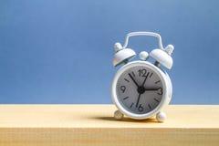 Witte kleine wekker op een houten plank op een grijze pastelkleurachtergrond minimalism stock afbeelding