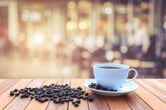 Witte koffiekop en koffiebonen op houten lijst met vage bac Stock Afbeeldingen