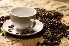 Witte koffiekop op een koffiezak met geroosterde rond bonen Royalty-vrije Stock Foto