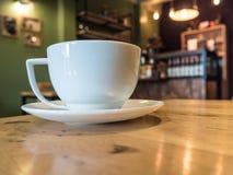 witte koffiekop op houten bureau in de winkel van de koffiekoffie Royalty-vrije Stock Afbeelding
