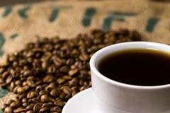 Witte koffiekop van koffie, op een koffiezak met geroosterde bonen Stock Foto's