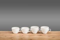 Witte koffiekoppen op de houten lijst Stock Afbeeldingen