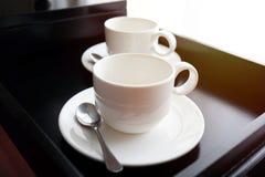 Witte koffiemok met lepel op zwart dienblad stock afbeeldingen