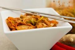 Witte kom Koreaans kimchivoedsel met eetstokjes stock afbeeldingen