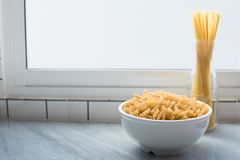 Witte kom van spiraalvormige macaroni en gebonden spaghettitribune recht bij stock foto