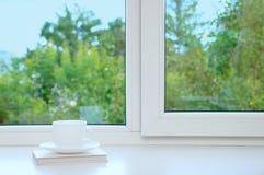 Witte kop en schotel op het venster royalty-vrije stock afbeeldingen