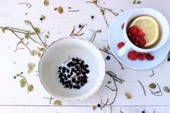Witte kop met de helft van citroen met groep rijpe rode framboos om een thee op ruwe bruine houten lijst te maken Stock Afbeeldingen