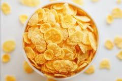 Witte kop met gouden die cornflakes, op witte achtergrond worden ge?soleerd Hopya rond de kop wordt afgebrokkeld die Mening van h royalty-vrije stock fotografie