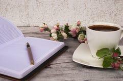Witte kop met koffie en mooie bloemen royalty-vrije stock afbeeldingen