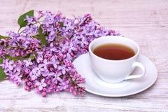 Witte kop met koffie of thee en een boeket van seringen op een houten achtergrond stock foto's